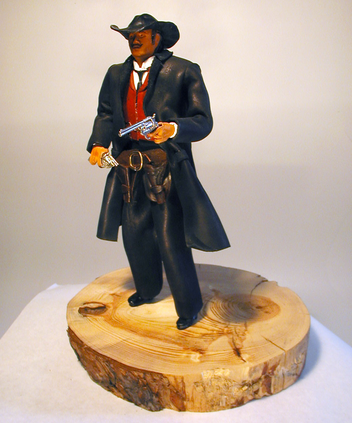 leather cowboy sculpture holding pistol